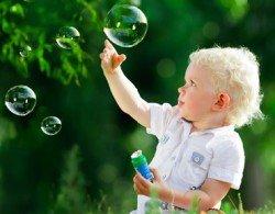 Ребенок летом пускает мыльные пузыри.